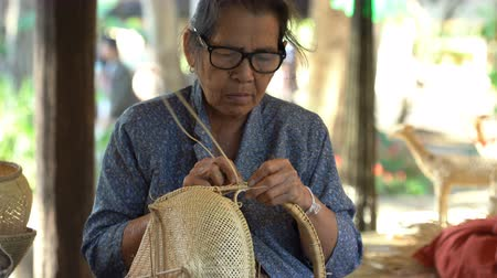 bamboo basket : NAKHON RATCHASIMA, THAILAND - DECEMBER 31, Unidentified woman weaving a bamboo basket.