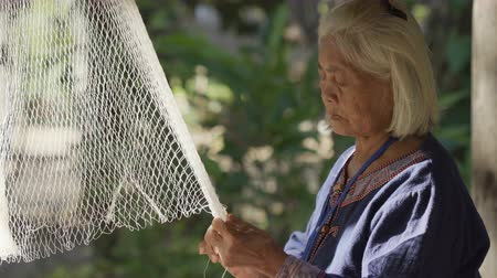 узел : NAKHON RATCHASIMA, THAILAND - DECEMBER 31, Unidentified woman weaving a fishing nets.