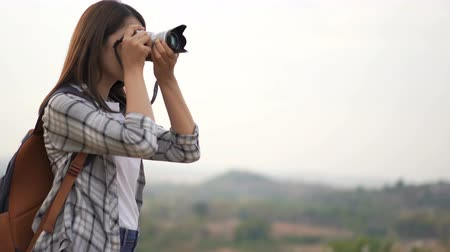 mirrorless : tourist woman taking a photo with her camera in nature