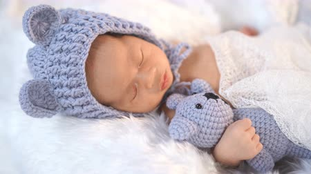 плюшевый мишка : newborn baby in bear hat sleeping on a fur bed Стоковые видеозаписи