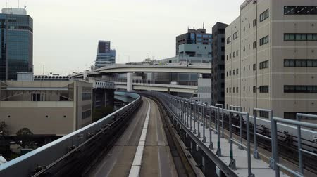 tokyo station : TOKYO, JAPAN - MARCH 28, 2019; Scenery of a train traveling on the rail of Yurikamome Line in Tokyo from Shimbashi station to Odaiba. Stock Footage