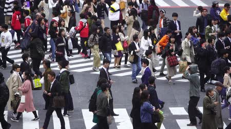 keresztül : TOKYO, JAPAN - March 25, 2019: slow-motion of people walking across at Shibuya famous crossing street in Tokyo, Japan