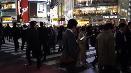 cartelloni : TOKYO, JAPAN - March 25, 2019: slow-motion of people walking across at Shibuya famous crossing street in Tokyo at night, Japan Filmati Stock