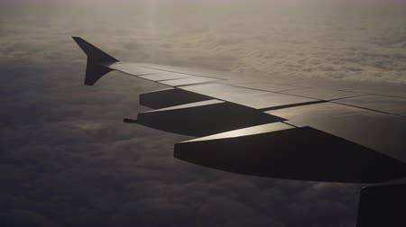 aeroespaço : Wing of airplane flying above the clouds in the sky with sunlight