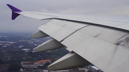авиационно космический : Wing of airplane flying in the sky while landing at the airport Стоковые видеозаписи