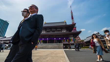 芝 : TOKYO, JAPAN - March 25, 2019: Time lapse of Unidentified tourists visit in ancient Zojoji temple with Tokyo tower background, This is a famous place in Tokyo, Japan.