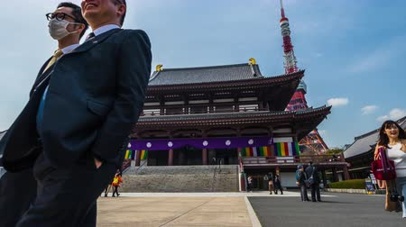 sótão : TOKYO, JAPAN - March 25, 2019: Time lapse of Unidentified tourists visit in ancient Zojoji temple with Tokyo tower background ,This is a famous place in Tokyo, Japan.