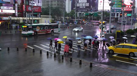 parasol : Taipei, Taiwan- 11 June, 2019: people crossing street in front of Ximending Shopping District with falling rain in Taipei, Taiwan. Ximending is the famous fashion, night Market and street food in Taipei.
