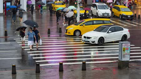taipei : Taipei, Taiwan- 11 June, 2019: time lapse of people crossing street in front of Ximending Shopping District with falling rain in Taipei, Taiwan. Ximending is the famous fashion, night Market and street food in Taipei.