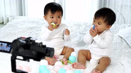 videocamera : two twin babies on a bed with video camera recording