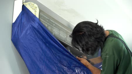 コンディショナー : slow-motion of technician service using water spray are cleaning the air conditioner indoors