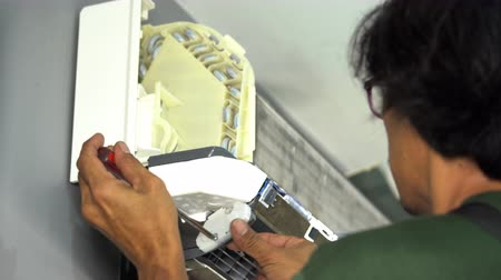 配線 : Nakhon Ratchasima, Thailand – Sep 1, 2019 : Technician service using screwdriver to repairing air conditioner indoors. 動画素材