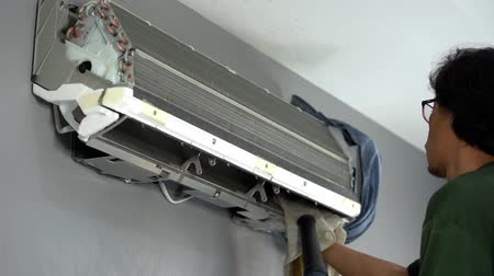 huishoudelijke apparaten : Nakhon Ratchasima, Thailand – Sep 1, 2019 : slow-motion of technician service using electric blowers to dry up and dust cleaning the air conditioner