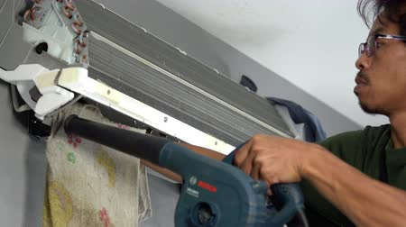 installer : Nakhon Ratchasima, Thailand – Sep 1, 2019 : Technician service using electric blowers to dry up and dust cleaning the air conditioner