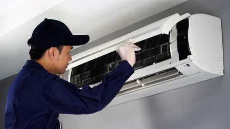 installer : technician service checking and repairing air conditioner indoors