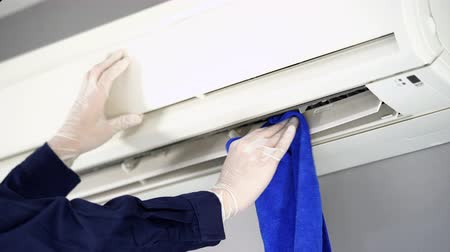 installer : close up technician service cleaning the air conditioner with cloth