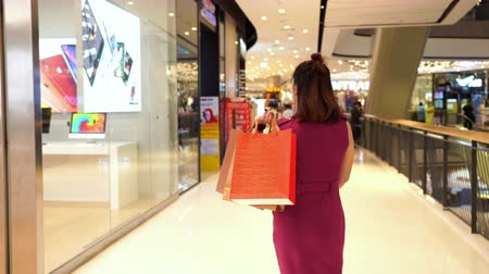 fashion outlet : NAKHON RATCHASIMA, THAILAND - SEP 27, 2019 : Young woman walking with shopping bags in the mall.