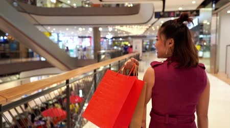 fashion outlet : slow-motion of young woman walking with shopping bags in the mall