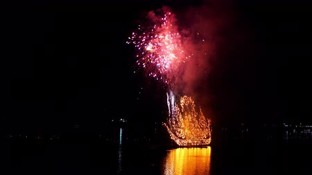 ラオス : NAKHON PHANOM, THAILAND - OCTOBER 13, 2019: Traditional fire boat floating with firework in Mekong river at night in Nakhon Phanom, Thailand