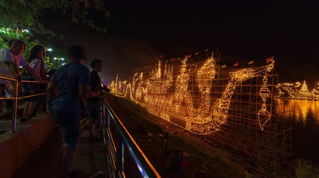 nakhon : NAKHON PHANOM, THAILAND - OCTOBER 13, 2019: time lapse of people visit traditional fire boat floating in Mekong river at night in Nakhon Phanom, Thailand