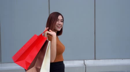 消費者運動 : slow-motion of happy woman walking with shopping bags