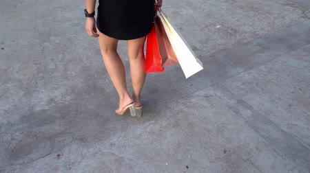 back side : slow-motion of female legs walking with shopping bags