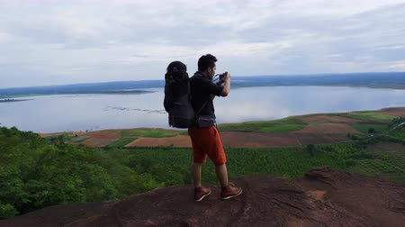 viewfinder : man traveler with backpack using camera taking a photo on the edge of cliff, on a top of the rock mountain