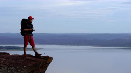 fotoğrafçı : man traveler with backpack using camera taking a photo on the edge of cliff, on a top of the rock mountain