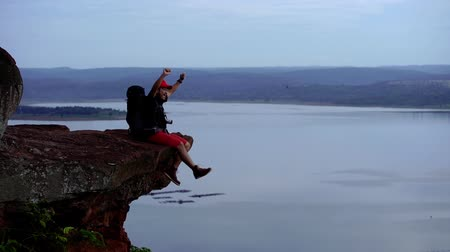 sırt çantasıyla : slow-motion of cheerful hiker man sitting and gesture raised arms on the edge of cliff, on a top of the rock mountain Stok Video