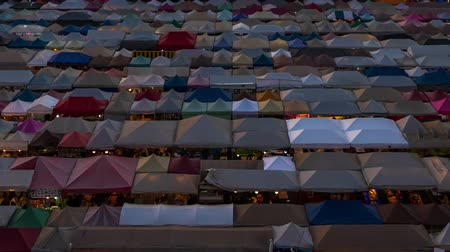rothadás : Bangkok, Thailand - Dec 6 ,2019 : day to night time lapse of Train Night Market Ratchada (Talad Rot Fai). market with plenty of shops with colorful canvas roofs at night in Bangkok, Thailand Stock mozgókép