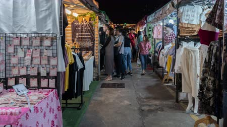 economico : Bangkok, Thailand - Dec 6 ,2019 : hyperlapse of Tourist and locals walking and shopping at Ratchada Night train market (Talad Rot Fai). market with plenty of shops with colorful canvas roofs at night in Bangkok, Thailand