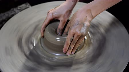 oleiro : Potters hands are creating a jar or vase of earthenware on potters wheel