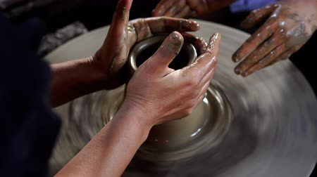 craftswoman : Potters hands are creating a jar or vase of earthenware on potters wheel