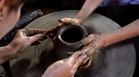 moldagem : Potters hands are creating a jar or vase of earthenware on potters wheel