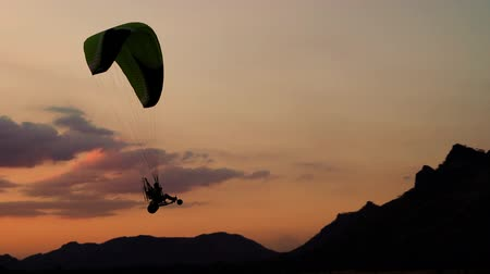 szybowiec : LOPBURI, THAILAND - JAN 4, 2020 : slow-motion of Paraglider flying against a sky at sunset over Khao Jeen Lae mountain in Lopburi, Thailand Wideo