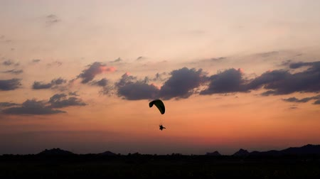 szybowiec : slow-motion of Paraglider flying against a sky at sunset over Khao Jeen Lae mountain in Lopburi, Thailand