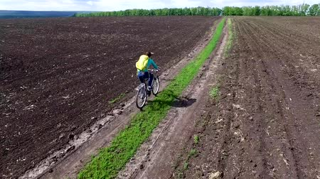 bycyclist riding bike in a field rolled road, aerial video
