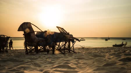 sunset view of pub table and chairs on african sandy beach with ocean and sky on the background, timelapse Stock Footage