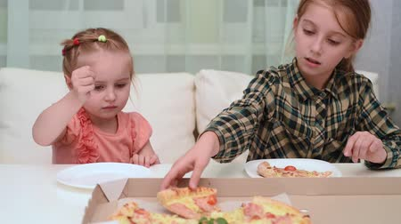 little girl giving a piece of fresh pizza from box to her younger sister, video
