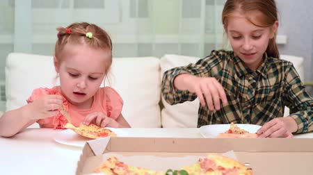 cute little girl eating pizza and her older cheerful sister waving her hand, video