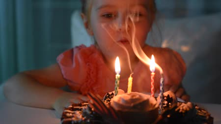 cute little girl blowing out candles on her beautiful birthday cake, video