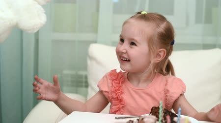 pretty cheerful little girl getting white hare toy at her birthday table with cake, video