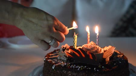 woman hand lighting candles on birthday chocolate cake with match, video Stock Footage