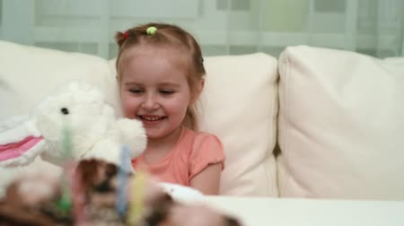 happy little girl playing her beautiful white hare toy at birthday table, video