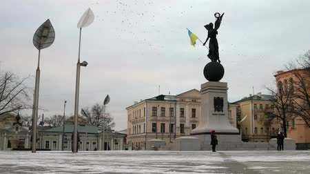 Constitution square in Kharkiv, Ukraine, blue and yellow flag waving on a monument, timelapse