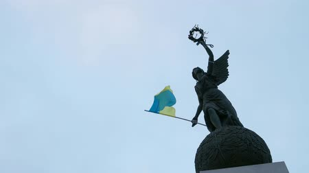 Ukrainian flag fluttering on wind on the independence monument in kharkiv, ukraine, slow motion