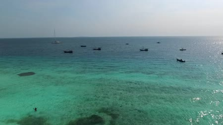 Fishermens boats near the touristic beach in Zanzibar, Tanzania, clear blue waters, aerial Stock Footage