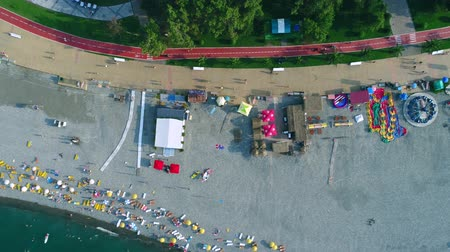 escala : Batumi, Georgia - 27 August 2017: Aerial drone shot of amusement park situated on the beach with bicycle lane on the sea coastline and people relaxing near sea