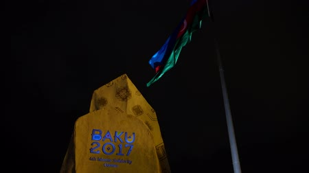 Baku, Azerbaijan - January 01, 2018: Monument of Islamic Solidary Games with national flag of Azerbaijan waving on the wind at night Стоковые видеозаписи