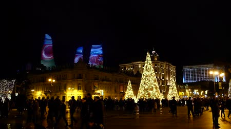 Baku, Azerbaijan - January 01, 2018: People walking on the square enjoying Baku at night. Flame Towers with color of national flag of Azerbaijan on the background. New Years celebration.